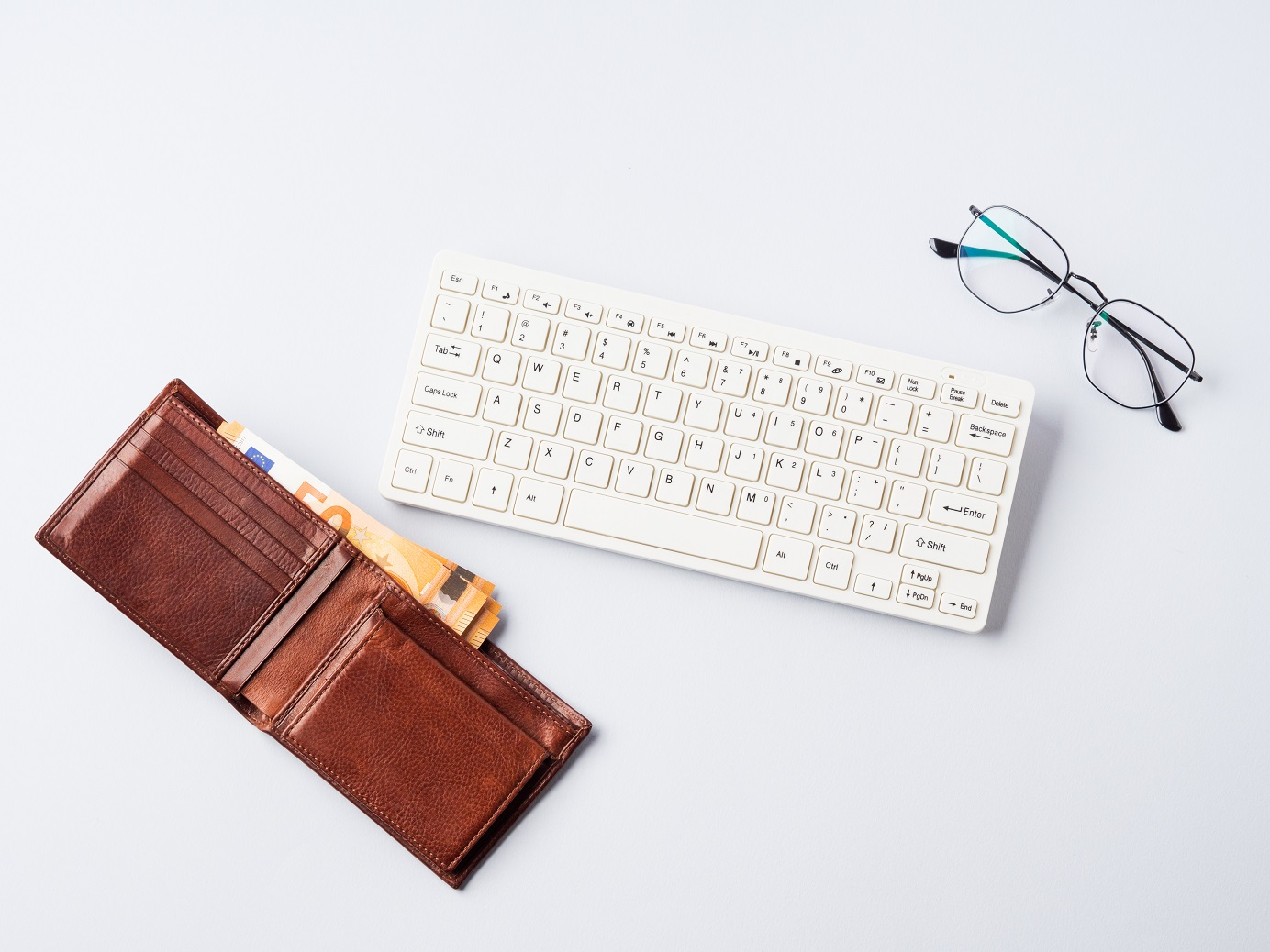 Euro money banknotes in wallet, keyboard and glasses. Online banking, business, student loan concept, financial online investment, smart trading, income earnings concept.